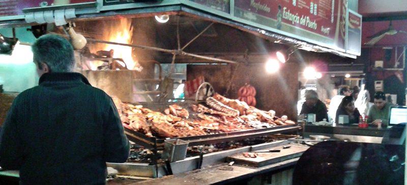Churrasco (parrillada) sendo preparado à vista dos clientes, no Mercado do Porto, em Montevidéu.