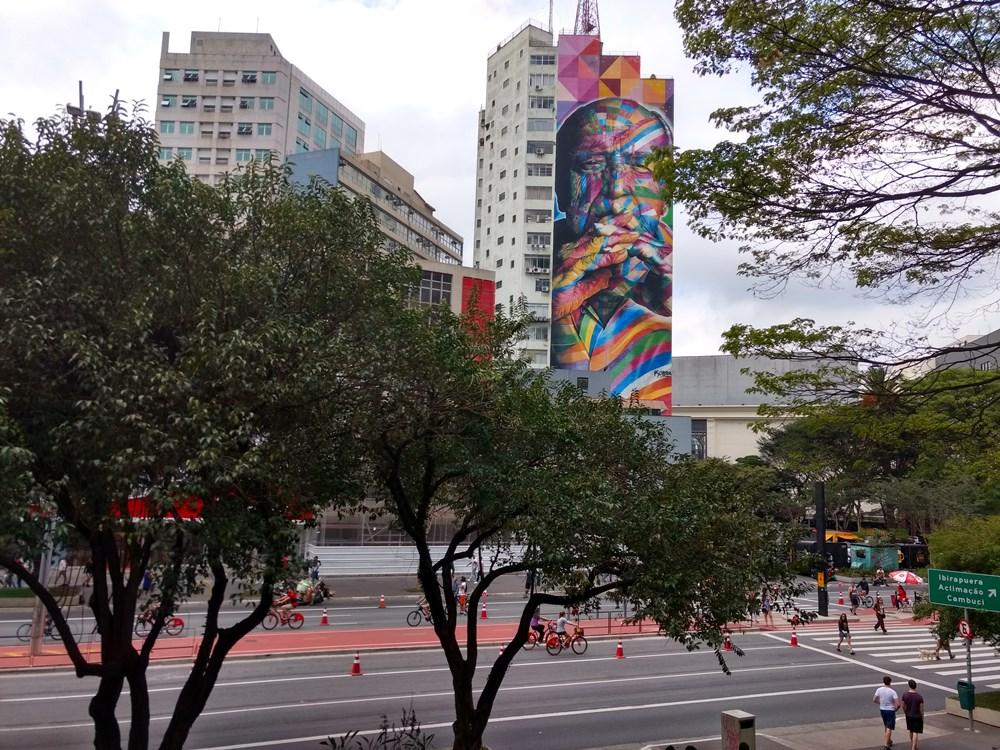 Avenida Paulista aberta, com ciclistas aproveitando o domingo. Aos fundos, painel de Oscar Niemeyer, obra o artista Eduardo Kobra.
