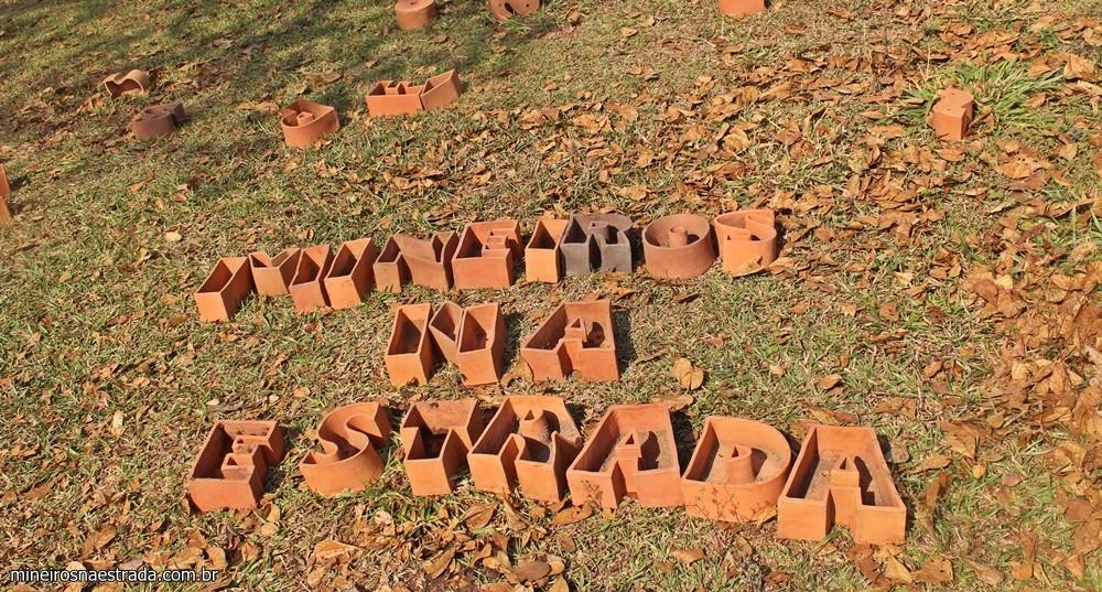 Galeria Marilá Dardot. Há terra e sementes para se cultivar nos vasinhos em forma de letras.