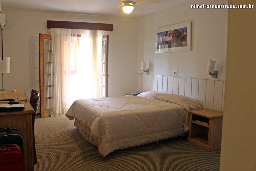 Suíte máster do Monreale Resort Hotel. O quarto conta com cama queen, mesa de trabalho, tv, telefone, cofre, frigobar e ar condicionado.