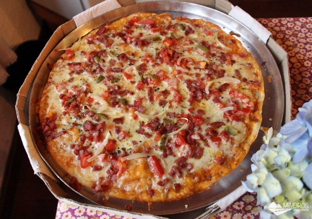 Pizza servida na Pousada do Rio, uma pousada em meio a montanhas, na zona rural de Gonçalves.