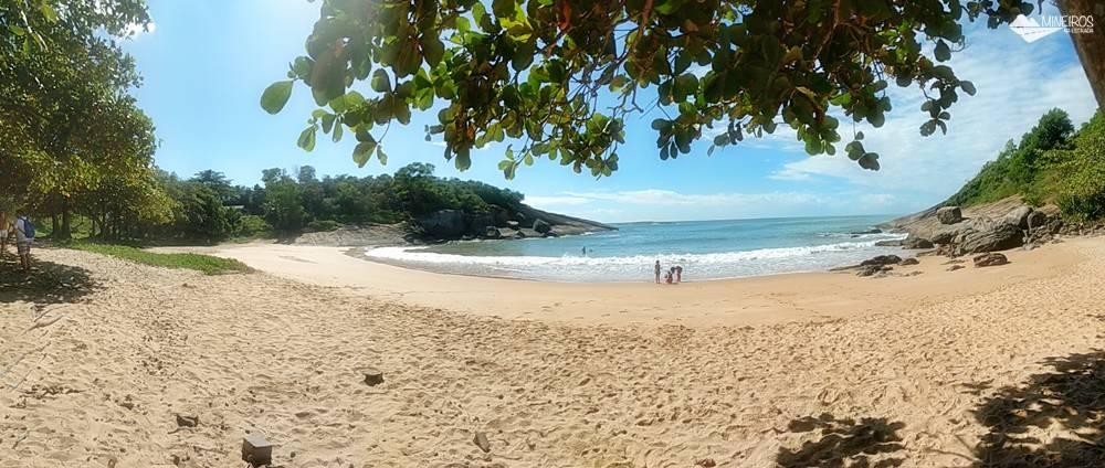 Praia dos Padres, em Guarapari., uma praia calma, sem quiosques, com sombra de árvores e mar calmo.
