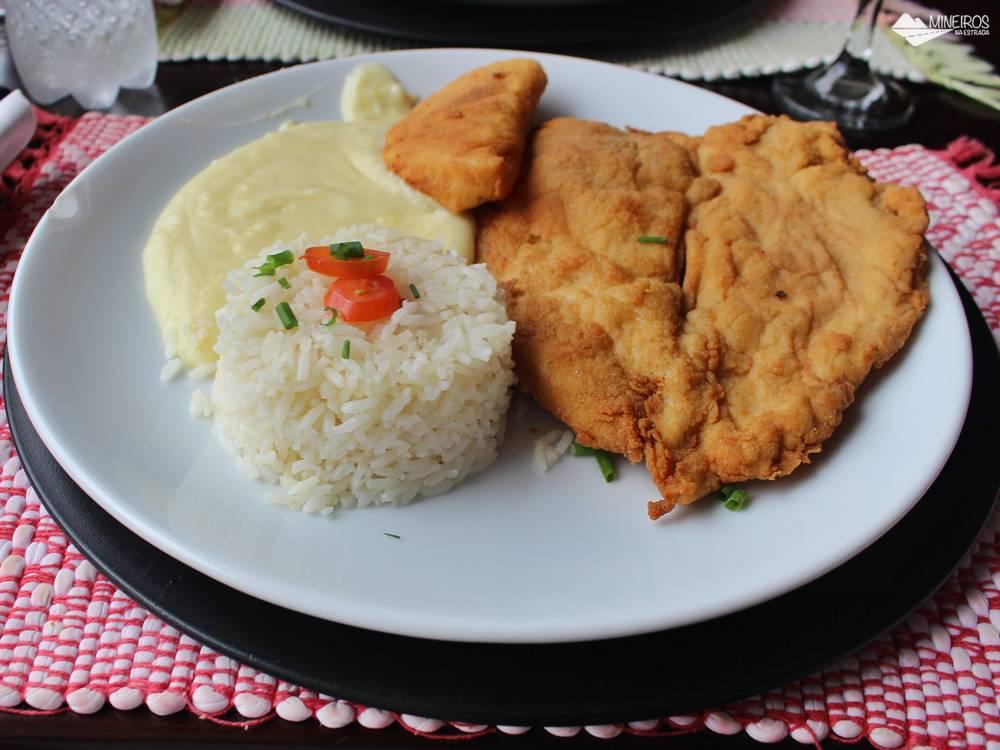 Refeição composta por frango à milanesa, abacaxi grelhado e purê de batatas, servida no restaurante Pucci, em Monte Verde.
